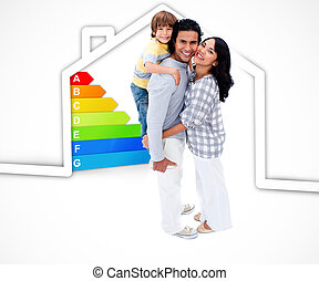 Smiling family standing with a house illustration with energy rating graphic on a white background