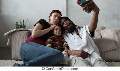 Smiling family taking selfie with mobile phone.