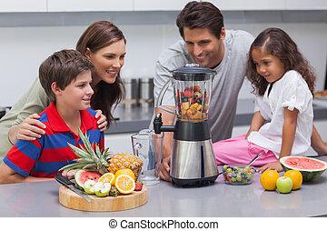 Smiling family using a blender