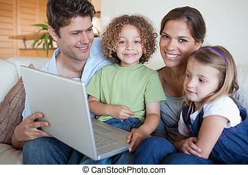 Smiling family using a laptop