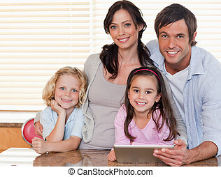 Smiling family using a tablet computer together