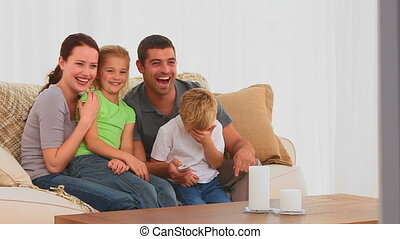 Smiling family watching a movie in the living room