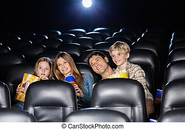 Smiling Family Watching Film In Theater
