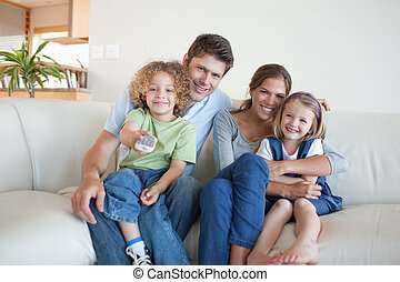 Smiling family watching TV together in their living room