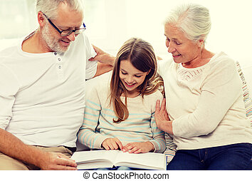 smiling family with book at home - family, generation and...