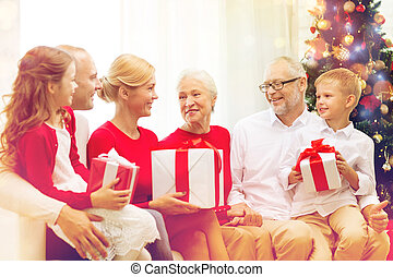 smiling family with gifts at home - family, holidays,...