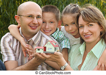 smiling family with two children is keeping wendy house in their hands and looking at camera. focus on boy\'s face. wendy house in out of focus.