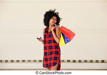 smiling farina american woman with bags and cellphone - ...