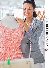 Smiling fashion designer adjusting dress on a mannequin