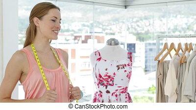 Smiling fashion designer looking at