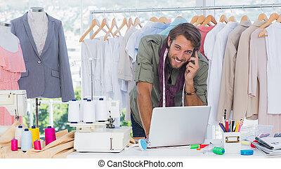 Smiling fashion designer using lapt
