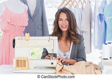 Smiling fashion designer using sewing machine and sitting ...