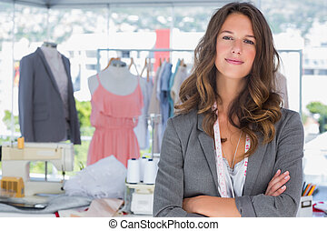 Smiling fashion designer with arms folded