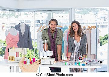 Smiling fashion designers leaning o