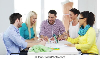 smiling fashion designers working in office