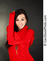 Smiling fashion woman in red dress on black background in studio