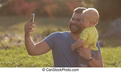 Smiling father and baby son making selfie in park