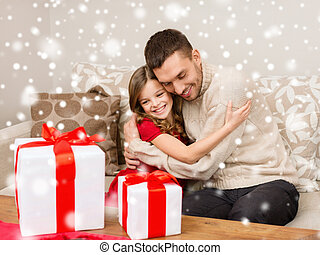 smiling father and girl with gift boxes hugging