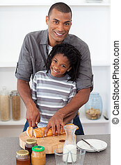 Smiling father and his son cutting bread