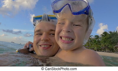 Smiling father and son bathing in the sea