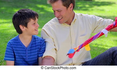 Smiling father and son looking at a kite