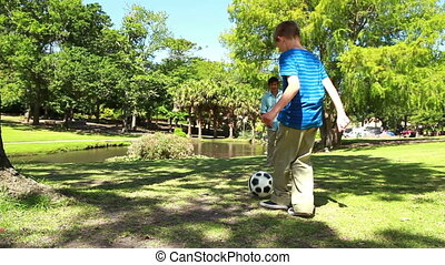 Smiling father and son playing soccer together