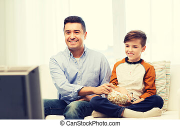smiling father and son watching tv at home