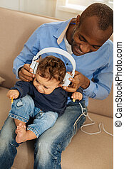Smiling father listening to music with his baby
