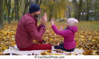 Smiling father playing clapping game with kid - Smiling...