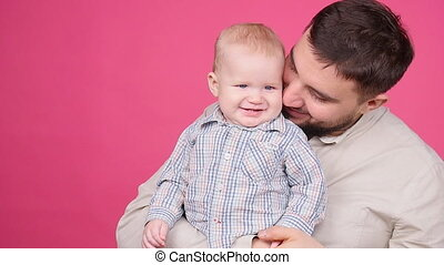 Smiling Father Playing With Baby Son