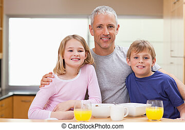 Smiling father posing with his children in the morning