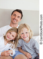 Smiling father sitting on the bed with his children