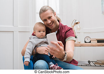 smiling father taking selfie with adorable son at home