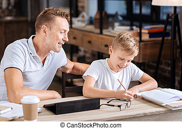 Smiling father watching his son make notes