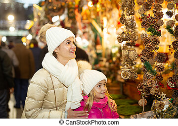 Smiling female and her daughter are choosing decorations for Christmas tree in the market outdoor