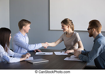 Smiling female and male partners handshaking satisfied with cont