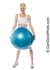 Smiling female athlete holding a big blue ball