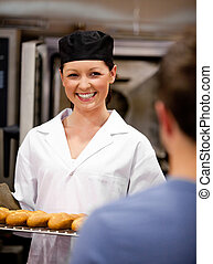 Smiling female baker holding baguettes ready to serve her customer in a bakery