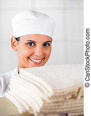 Smiling Female Baker With Bread Slices In Bakery