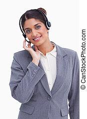 Smiling female call center agent adjusting her headset