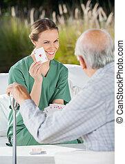 Smiling Female Caretaker Showing Ace Card To Senior Man