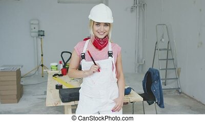 Smiling female carpenter standing at workbench - Gorgeous...
