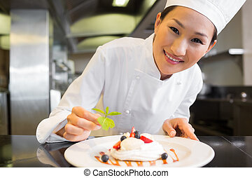Smiling female chef garnishing food in kitchen - Closeup of...