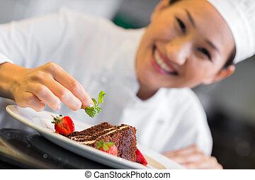 Smiling female chef garnishing food