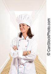 Smiling female chef in a corridor