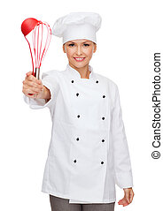 smiling female chef with cooking equipment