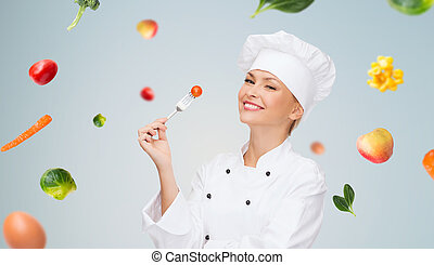 smiling female chef with fork and tomato - cooking and food...