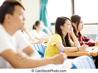 smiling female college student sitting  with classmates