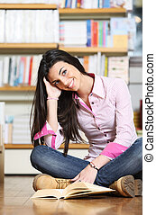 smiling female college student sitting on floor in library, reading book
