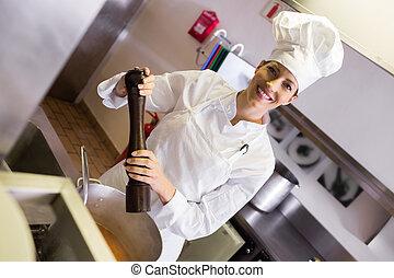 Smiling female cook preparing food in kitchen